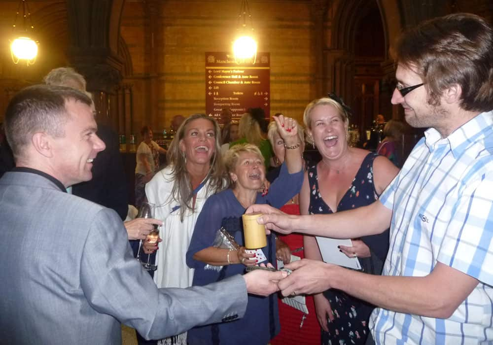 Manchester Town Hall: Wedding day magic. Pickpocketing a watch revelation moment in cup and ball trick.